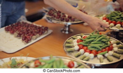 Preparing for catering, vegetables and desserts on trays -...