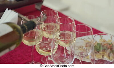 Waiter pours white wine in glasses on a banquet