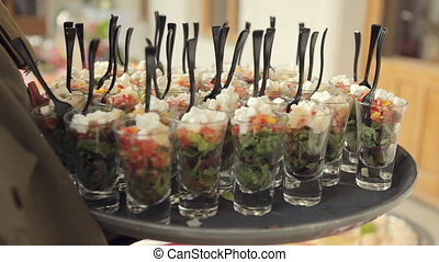 Waiter puts vegetable salad in individual containers on the...