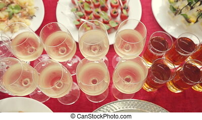 Row of the glasses with alcohol and juice, a wide variety of snacks at the banquet