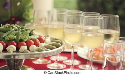 Vegetables on a tray and alcohol poured into glasses at a...