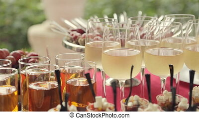 Glasses of wine, juice, desserts and snacks at the banquet -...