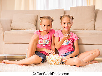 Twin sisters - Twins sisters are watching tv and eating...