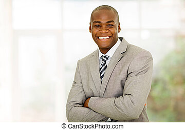 african businessman with arms folded in office
