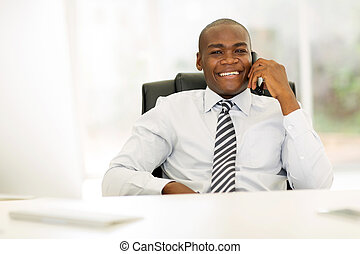 african business man talking on landline phone in modern...