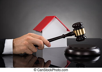 Judge With House Model Hitting Gavel - Close-up Of Judge...