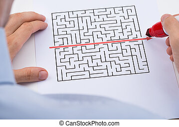 Person Drawing Straight Red Line Over Maze - Close-up Of...