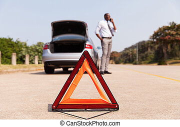 african male driver calling for help after car broke-down by...