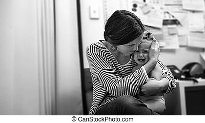 Young mother hugs a crying toddler in hospital. Child...