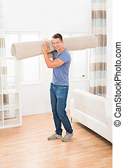 Man Carrying Rolled Carpet - Portrait Of Happy Young Man...