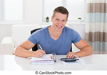 Man Doing Calculation At Home - Portrait Of Happy Man Doing...