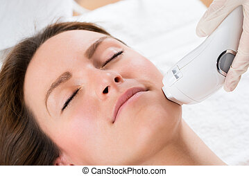 Beautician Giving Laser Epilation Treatment To Woman Face
