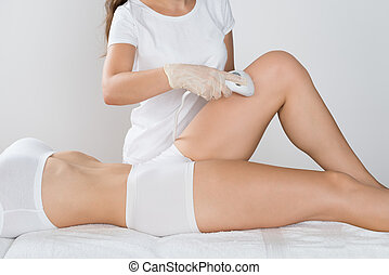 Woman Having Laser Treatment On Thigh - Close-up Of Young...