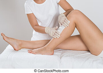 Beautician Waxing Leg Of Woman With Wax Strip At Beauty...