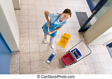 Janitor Holding Mop With Cleaning Equipments And Wet Floor...