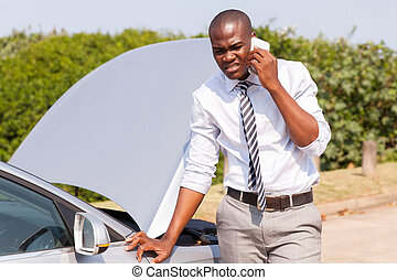 young african man calling for assistance with his car broken...