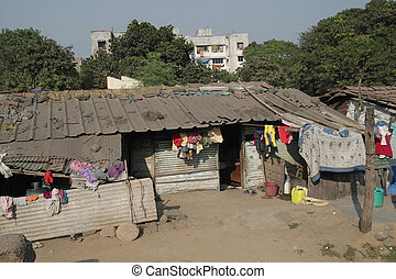 Poverty - Makeshift housing besides apartment in India