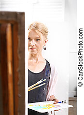 A painter in her studio - An artist in front of the easel