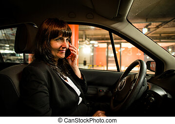 Calling phone- senior business woman  in car