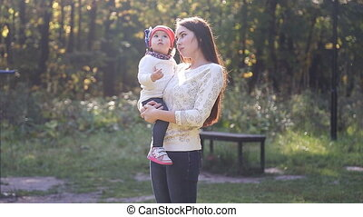 Mom and baby daughter for a walk in the autumn park