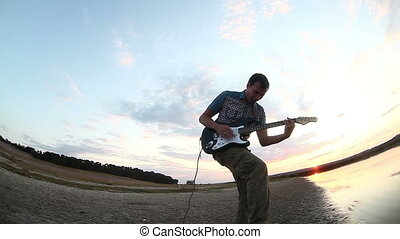 guitarist musician man playing solo on electric guitar by...