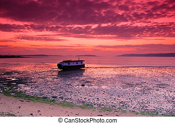 Lonely boat - A lone houseboat under a vibrant sunset sky....