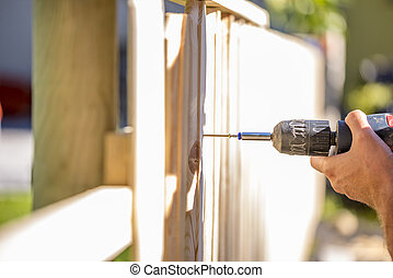 Man erecting a wooden fence outdoors using a handheld...