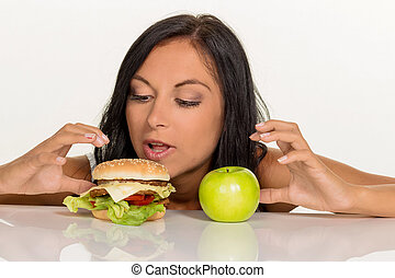 choosing between hamburger and apple - a young woman can not...