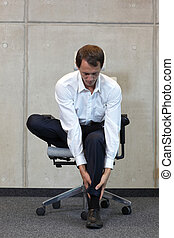 business man exercising on chair - office occupational...