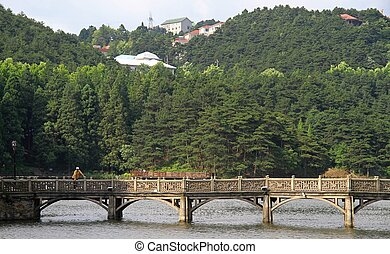 stone bridge on lake in national park of mountain Lu, China