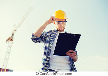 builder in hardhat with clipboard outdoors - business,...