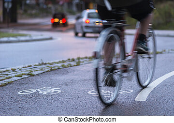 Cyclist in blurred motion on cycling path by busy street at...