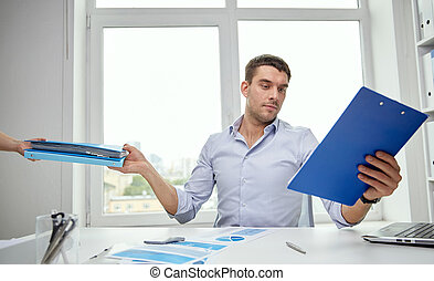 businessman taking papers from secretary in office -...