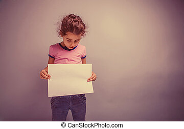 girl child 6 years of European appearance holds a blank slate