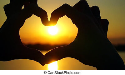 Woman makes heart hands directs the sunset - Woman makes...