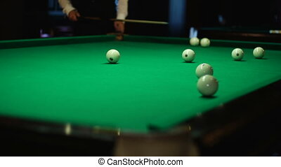The player hits the ball in billiards