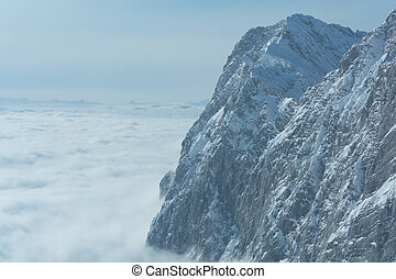 Mountaintop in the Dachstein area above sea of fog -...