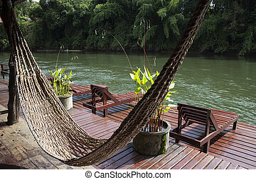 Hammock hanging at the balcony beside the river