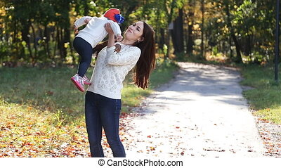 Mom and baby daughter for a walk in the autumn