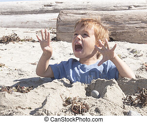 young child buried in the sand.