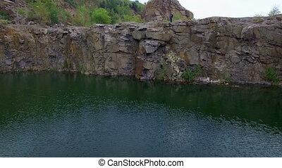 Aerial: Man takes photos on rocks