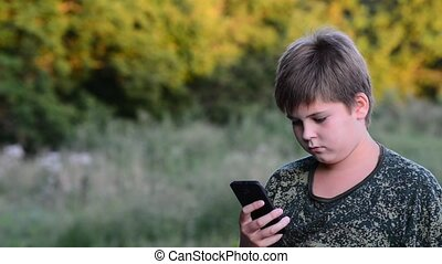 Teenage boy uses  smartphone  in the open air