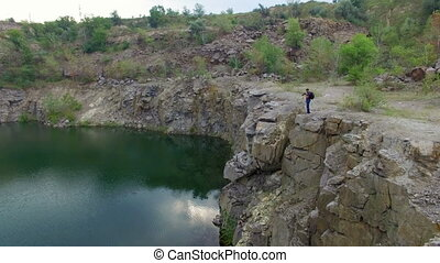 Aerial: Man takes photos on rocks - Aerial: Man takes photos...