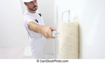 painter man at work, with roller painting wall, painter...