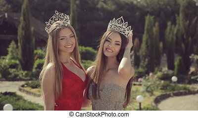 Two beautiful young girls in crowns and evening dresses...