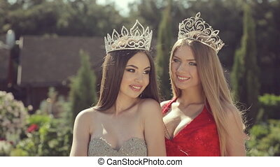 Two wonderful long-haired beauties in crowns standing in a...
