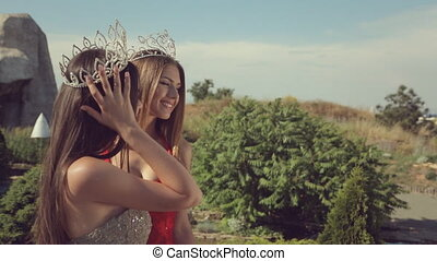 Two young women with long hair and the expensive crowns on...
