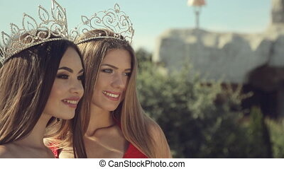 Two gorgeous girls with long hair and crown with jewels on...