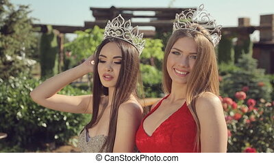 Two young beauty contest winner in long evening dresses and...