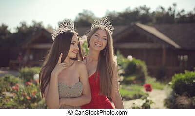 Two amazing girls in a long gowns and crowns laughing in the...